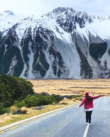 woman walking in front of mountain peak