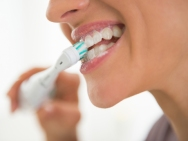 closeup on young woman brushing teeth